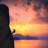 Climber against sunset Stock Photo