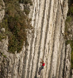 Climber ascending  difficult stone wall Stock Images