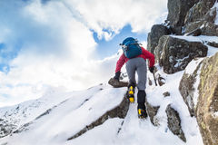 A climber ascending a snow covered ridge Royalty Free Stock Photo