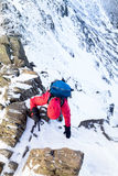 A climber ascending a snow covered ridge Stock Photography