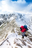 A climber ascending a snow covered ridge Stock Images