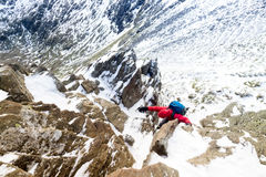 A climber ascending a snow covered ridge Stock Image