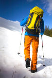 Climber with a backpack climbs the snow. Royalty Free Stock Photo