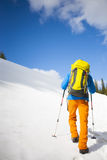 Climber with a backpack climbs the snow. Royalty Free Stock Photos