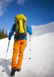 Climber with a backpack climbs the snow. Royalty Free Stock Image