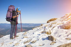 Climber with a backpack is on a slope. Stock Photography