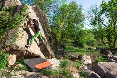 Climber is bouldering outdoors. Climber is bouldering in nature. Girl climbs on a big stone. Woman doing sports outdoors. Athlete is engaged in activity Royalty Free Stock Photos