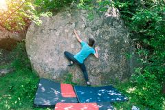 Climber is bouldering outdoors. Climber is bouldering in nature. Girl climbs on a big stone. Woman doing sports outdoors. Athlete is engaged in activity Stock Photos