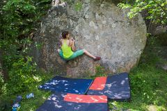 Climber is bouldering outdoors. Royalty Free Stock Image