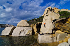 Climber bouldering in Sardinia. Free climber bouldering surrounded by the sea in Capo Testa, Sardinia, Italy Stock Photography