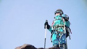 A climber in a bright suit stands on the mountain top and raises his hands with ski poles up and happy stock video footage