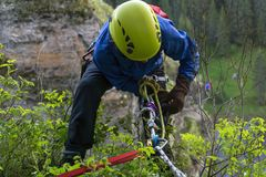 Checking the reliability of the safety rope. Climber checks the reliability of his safety system before descending from the cliff royalty free stock photos