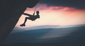 Climber on a cliff against misty mountains. Instagram stylisation royalty free stock image