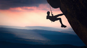 Climber on a cliff against misty mountains royalty free stock photo