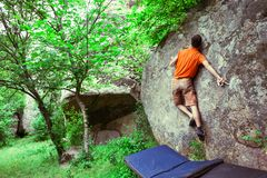 The climber is climbing bouldering. The climber climbs the stone. The athlete is engaged in bouldering. Rock climbing in nature Stock Photography