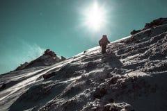 Climber climbing on an icy hill Royalty Free Stock Photos