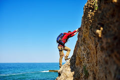 Climber climbing on mountain. Climber with backpack climbing on top of mountain Stock Photography