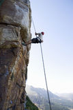 A climber climbing a rock face Stock Photo