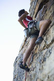 A climber climbing a rock face Stock Photography