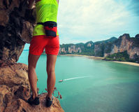Climber climbing at seaside cliff Stock Photos