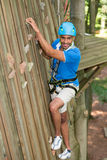 Climber in climbing wall at high rope course Royalty Free Stock Image