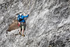 A climber climbs alone on top of a rock face stock photo