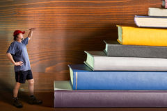 Climber climbs a heap of books Royalty Free Stock Images