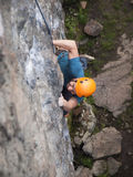 The climber climbs in the helmet on the wall. Stock Image