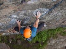 The climber climbs in the helmet on the wall. Stock Photos