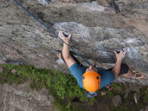 The climber climbs in the helmet on the wall. Royalty Free Stock Photography