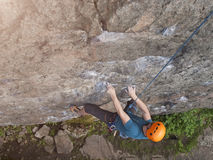 The climber climbs in the helmet on the wall. Stock Photography
