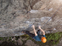 The climber climbs in the helmet on the wall. Royalty Free Stock Image