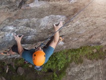 The climber climbs in the helmet on the wall. Stock Photo