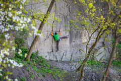 Climber climbs on the rock. A man goes in for sports in the fresh air. The athlete climbs on the boulder Stock Photography