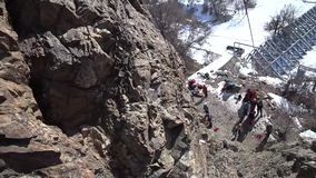 Climber climbs the rock. First person view. The camera on the helmet. Extreme climbing. Visible rope, hands and bare stones. Gray rock. Danger of falling stock video footage