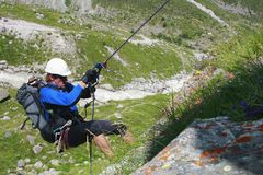 The climber climbs the rock by the rope. Big backpack, helmet, various equipment. Sunny day, mountain valley with alpine meadows and flowers. Below is a Royalty Free Stock Image