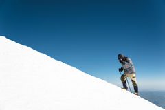 The climber climbs the snow-covered summit. Royalty Free Stock Images