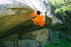 The climber is climbing bouldering. The climber climbs the stone. The athlete is engaged in bouldering. Rock climbing in nature Royalty Free Stock Images