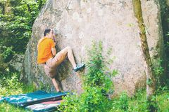 The climber is climbing bouldering. The climber climbs the stone. The athlete is engaged in bouldering. Rock climbing in nature Stock Images