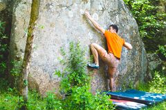 The climber is climbing bouldering. The climber climbs the stone. The athlete is engaged in bouldering. Rock climbing in nature Stock Photo