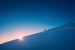 A climber climbs up a snowy slope. Sunset sky on a horison Stock Image