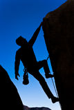 Climber clinging to a cliff. Stock Photos