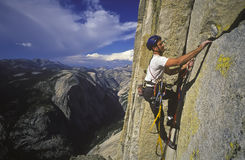 Climber clinging to a cliff. Climber ascends a steep crack on Half Dome in Yosemite National Park, California Stock Photography