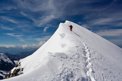 Descending climber. Climber descending snowy peak at mountains Royalty Free Stock Images
