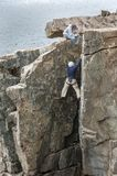 Climber feeling for a handhold on Otter Cliff rock face Royalty Free Stock Photography