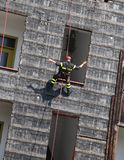 climber of firefighters rappelling the wall during the fire dril Stock Images