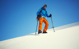 The climber goes on the snow slope. Stock Photo