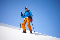 The climber goes on the snow slope. Royalty Free Stock Image