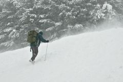 Climber going for the top in a snow storm Stock Image