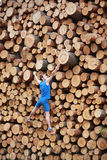 Climber going up the large pile of cut wooden logs Royalty Free Stock Image